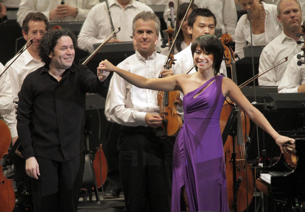 "Conductor Gustavo Dudamel, left, concertmaster Martin Chaulifer, center, and piano soloist Yuja Wang, right, at the L.A. Phil's performance at the Hollywood Bowl on Aug. 9, 2012. <br><a href=""http://articles.latimes.com/2012/aug/09/entertainment/la-et-cm-yuja-wang-dudamel-20120809"" target=""blank""><b>More:</b> Yuja Wang turns heads at the Hollywood Bowl with a purple gown</a> <a href=""http://www.latimes.com/entertainment/arts/culture/la-et-cm-0811-bowl-dudamel-wang-pictures,0,2936564.photogallery"">Photos</a>"