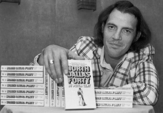 "Former Dallas Cowboy Peter Gent poses in 1974 with copies of ""North Dallas Forty,"" his bestselling book about playing in the NFL. Gent wrote of hard-living, hard-hitting pro football players, but he wrote with style: ""It was late afternoon. In a last gasp the sun had burned away the gray sky and had disappeared into the Panhandle. The air had warmed some and the best part of the day remained. Being in Texas is a skin feeling, strongest this time of day.... I love Texas, but she drives her people crazy. I've wondered whether it's the heat, or the money, or maybe both. A republic of outlaws loosely allied with the United States, Texas survives, and survives quite well by breaking the rules."""
