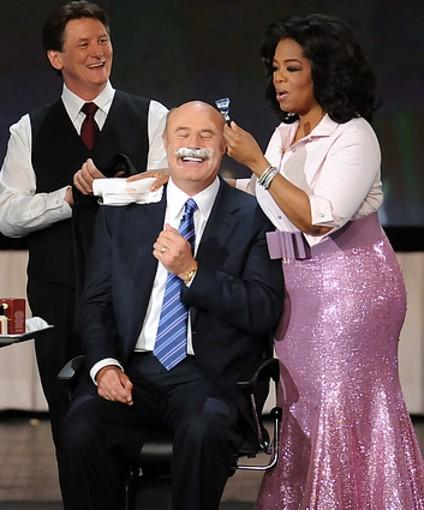 "In 1995, Oprah hired former psychologist Phil McGraw's consulting firm to help her navigate the Texas beef trial. After her victory, Oprah invited the straight-talking ""Dr. Phil"" on her show in 1998, effectively launching the mustachioed self-help mogul's television career. He soon became a weekly guest, appearing Tuesdays as a ""relationship and life strategy expert"" to offer advice on parenting, weight loss, financial planning and romance. In 2002, Dr. Phil graduated to his own show, produced by Winfrey's Harpo Studios.<br> <br> <I>Photo: Oprah helps shave Dr. Phil's trademark mustache during a live taping of ""The Oprah Winfrey Show"" on May 7, 2010 at Radio City Music Hall in New York.</i>"