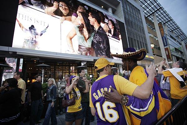 "Lakers fans embrace under the big screen showing celebrities and Michael Jackson fans arriving for the premiere of ""This Is It"" at L.A. Live. The Lakers and Clippers opened their seasons against each other at the Staples Center the same night."
