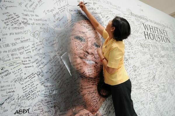 A fan of pop superstar Whitney Houston signs a giant mural with a portrait of her idol displayed at a mall in Manila.