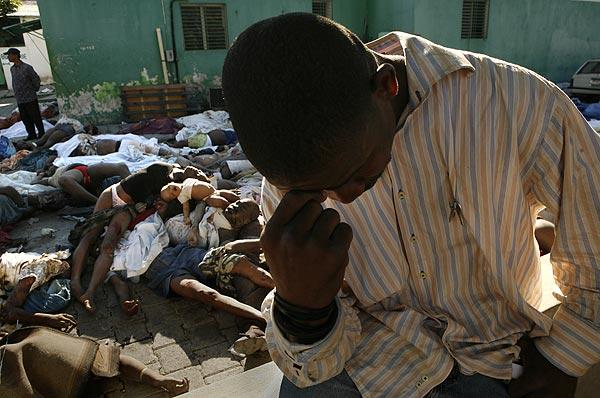 Lionel Michaud mourns the death of his wife, Lormeny Nathalie, and son Christian Michaud, who lie in the courtyard outside a morgue in Port-au-Prince where hundreds of bodies have been brought.