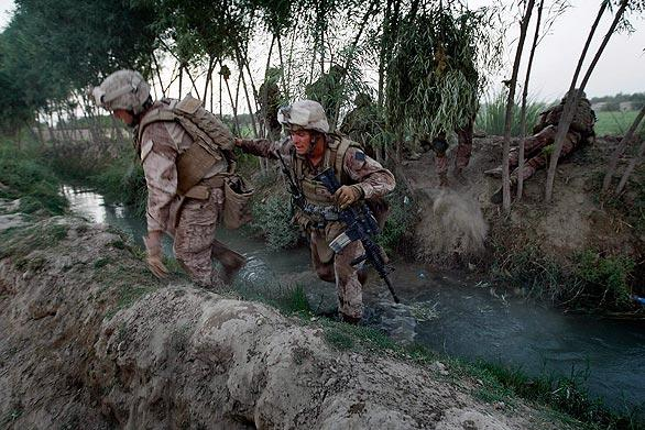U.S. Marines from 2nd Marine Expeditionary Brigade, RCT 2nd Battalion 8th Marines Echo Co. cross a canal as they conduct a sweep of a compound on July 4, 2009 in Mian Poshteh, Afghanistan.
