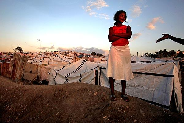 A Haitian woman eyes a man flirting with her as life goes on in a tent camp on the outskirts of Port-au-Prince.