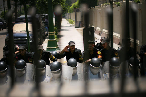 Anti-riot soldiers sit behind a gate barring entry to the Egyptian parliament in Cairo.