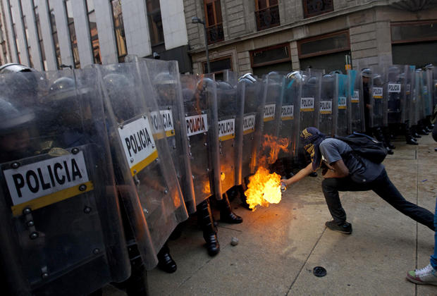 A demonstrator lights up a spray can next to riot police in Mexico City.
