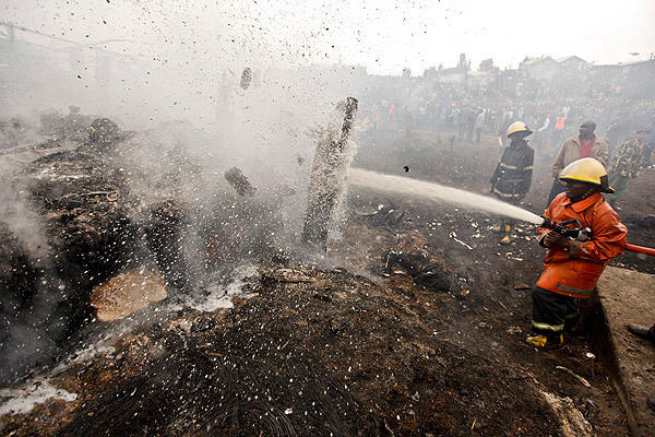 Firefighters try to put out smoldering wood after an explosion in a slum in Nairobi, Kenya. The explosion happened as people gathered to collect leaking gasoline. <i>(Note: Some of the images in this gallery may be disturbing to some readers.)</i>