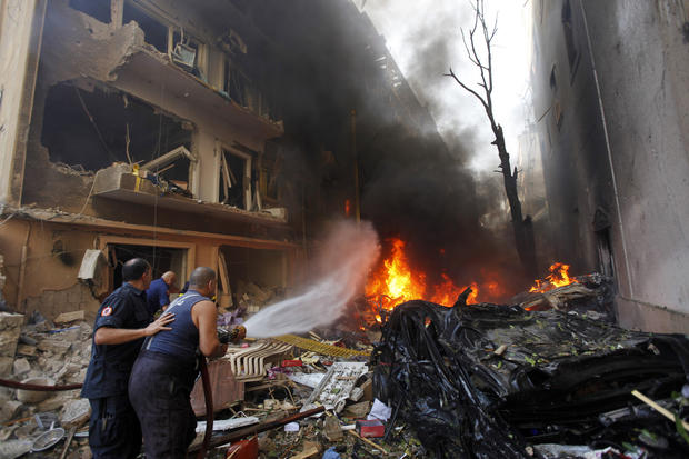 Lebanese firefighters extinguish burning cars at the scene of an explosion in the mostly Christian neighborhood of Achrafiyeh in Beirut.