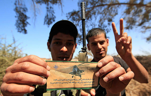 "A rebel holds a flier dropped by NATO aircraft on Kadafi troops that reads in Arabic, ""NATO forces will take all necessary measures to destroy military equipment that threatens civilians. Stop and stay away from fighting now or when you see this helicopter it will be too late,"" at the frontline in Dafniya, about 25 miles west of Misurata."