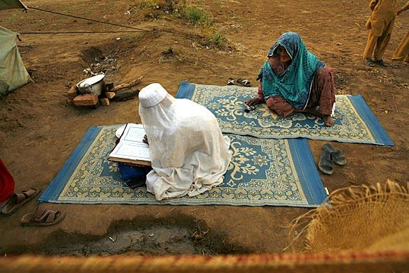 An elderly refugee, left, reads the Koran at the Little Lahore camp outside Swabi.  U.S. envoy Richard Holbrooke, who Friday wrapped up a three day visit to Pakistan, praised the military offensive but said gains could be lasting only if Pakistan and the international community focuses on reconstruction, so the people displaced can return safely to the lives they led.
