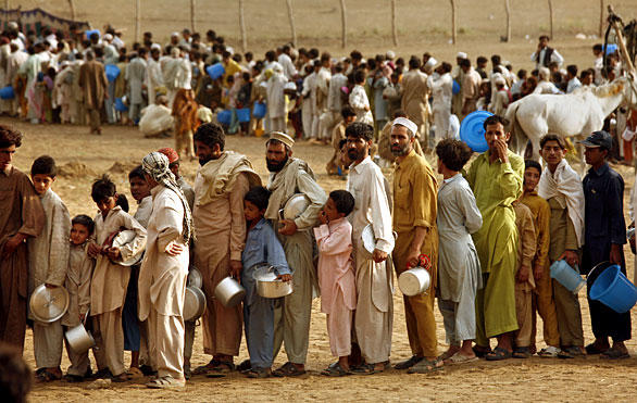 Some of the 25,000 displaced villagers at the Little Lahore camp queue for food. In Upper Dir, a district north of Swabi and adjacent to Swat, a suicide bomber struck during Friday prayers, killing 38 worshipers, including 14 children.