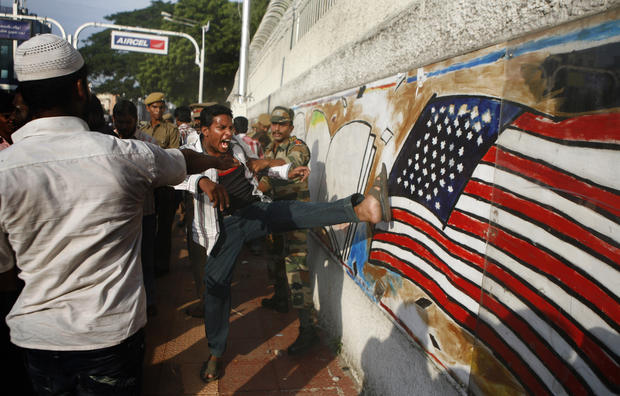 An Indian protester kicks at a graffiti of the American flag on a wall of the U.S. Consulate during a protest in Chennai against the anti-Islam film.