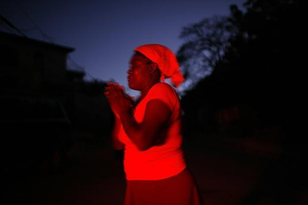 A woman prays at the break of dawn in Port-au-Prince. At night, rich and poor take to the streets to sleep, worried about being caught in their homes if aftershocks hit.