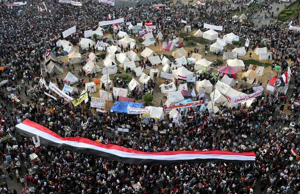 Egyptian protesters hold a giant national flag during a protest against President Mohamed Morsi at Tahrir Square.