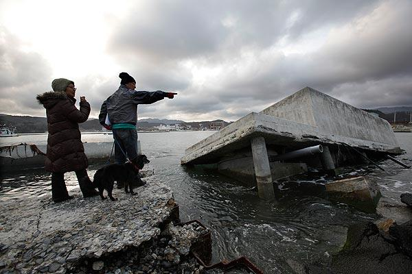 Nobuo Watanabe, right, and his wife, Seiko, with their dog look at a breakwater badly damaged by the last year's earthquake and tsunami in Minamisanriku, Japan, on Sunday. People across Japan prayed and stood in silence on Sunday to remember the massive disaster that struck the nation one year ago, killing more than 19,000 people and unleashing the world's worst nuclear crisis in a quarter century.