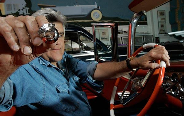 Jay Leno holds a starter switch bezel for the 1956 Packard Caribbean he keeps in his warehouse-sized Burbank garage, which houses his collection of more than 200 cars and motorcycles. A prototype for the hard-to-find auto part was designed and printed in plastic using a 3-D printer.