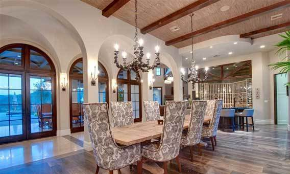 A pair of massive chandeliers provide lighting over the dining table.
