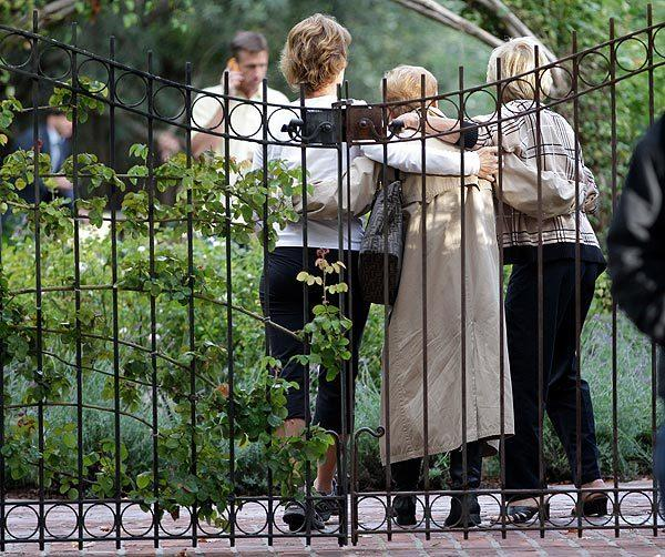 Unidentified women embrace before they enter Steve Jobs' house in Palo Alto, Calif., Wednesday. Jobs, the Apple co-founder and former CEO invented and masterfully marketed ever-sleeker gadgets that transformed everyday technology.