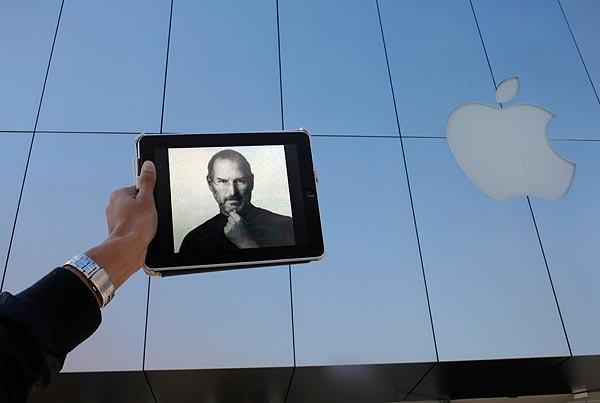 At the Apple store in Santa Monica, a man holds an iPad withSteve Jobs' image on the screen.