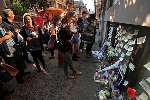 People gather at the Apple store in New York City's SoHo neighborhood, leaving messages and flowers for Steve Jobs, who died on Wednesday.