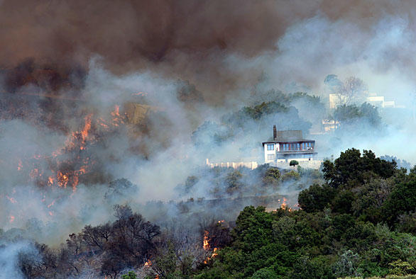 Smoke partly obscures the view of homes on San Roque Road in Santa Barbara.