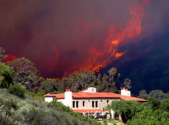 Flames loom behind a home on San Roque Road in Santa Barbara.
