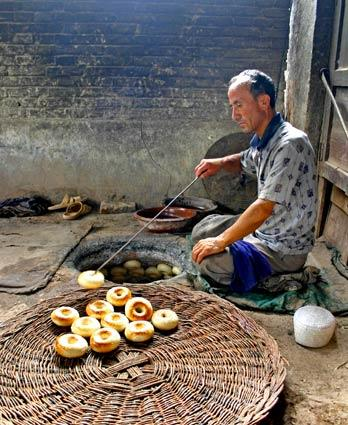 In a village in rural northwestern China, a bakery makes bagels, called <i>girda nan</i> or <i>nang</i>, by placing shaped dough along the sides of a very hot oven to bake. The finished bagels are removed with a metal tool to a hand-woven basket and delivered to street corner stands.