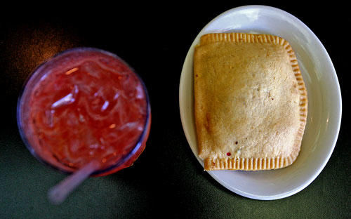 A Jamaican pattie filled with ground beef and Jamaican seasonings and a glass of passionfruit and pomegranate juice as served at Sattdown Jamaican Grill.