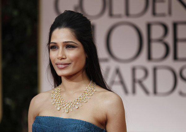 Freida Pinto's 145 carat yellow diamond Chopard choker ratchets up the style of her plain peacock blue Prada bustier dress.