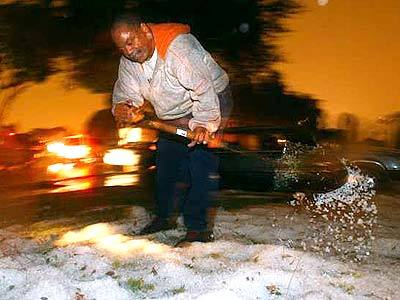 Gerald Pickens shovels hail from his front yard on Central Ave in South L.A.  A  rare storm battered parts of the Southland with rain and hail on Wednesday evening.