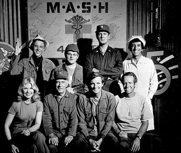 The cast of MASH in 1978.  Seated from left are Loretta Swit, Harry Morgan, Alan Alda and Mike Farrell.  Standing from left are William Christopher, Gary Burghoff, David Ogden Stiers and Jamie Farr.