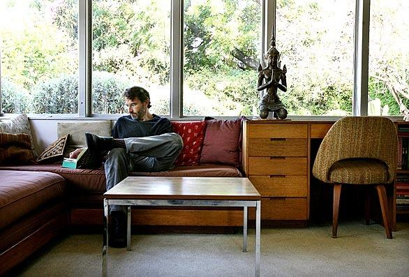 Architect John Bertram flips through a book at the historic Neutra home in Silver Lake that he lives in on Wednesday, July 22, 2009. Bertram has restored Neutra homes in his practice and designs homes that bear the influence of Neutra.