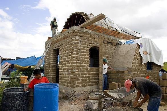 "Volunteers work on an adobe house near San Miguel de Allende, Mexico. The homes are the work of Casita Linda, a small organization similar to Habitat for Humanity made up of foreign retirees. Their goal: to help the local poorest of the poor by ""building hope, one house at a time."""