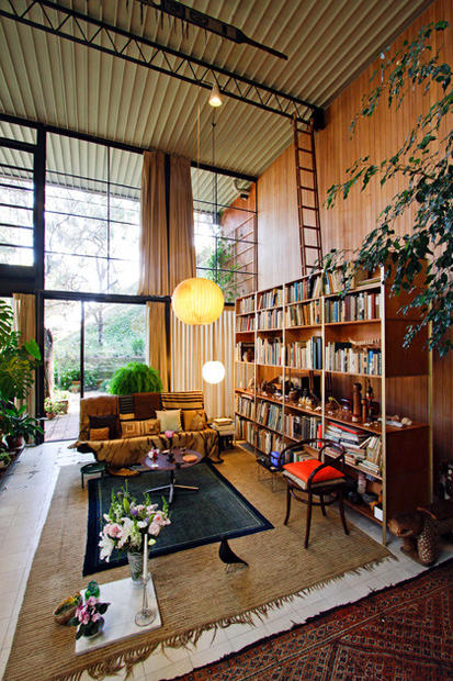 The bookcase was built at the Eames Office. The ladder reaching toward the corrugated steel ceiling allowed Charles to rearrange hanging light fixtures and string paintings face down, parallel to the floor, so if one were to look up, one would see a gallery on the ceiling.
