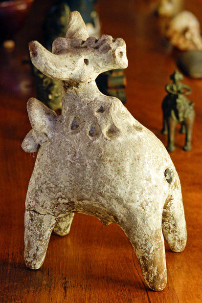 A white-painted terra cotta folk sculpture of Nandi, the bull of the Hindu god Shiva, sits on the living room bookcase.