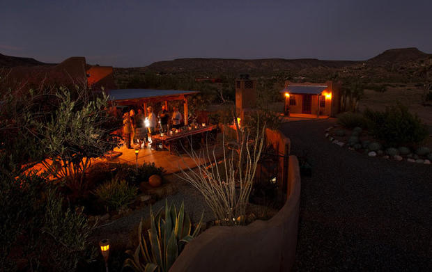 By David A. Keeps<br /> Friends gather by the flowing garden fireplace and outdoor dining table of the pueblo-style residence, whose generous patio spaces easily accommodate two-dozen. The guest house is on the right.