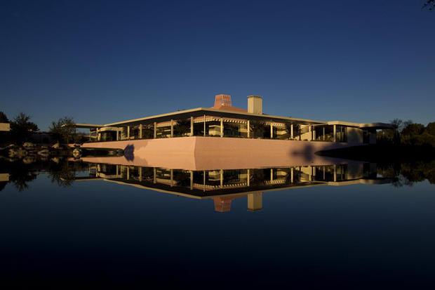Leonore Annenberg favored pink, which accounts for the pink roof and walls. She admired how the color washed over the surrounding mountains at sunset. Here, the house and one of its pink garden retaining walls is mirrored in one of Sunnylands 11 artificial lakes.