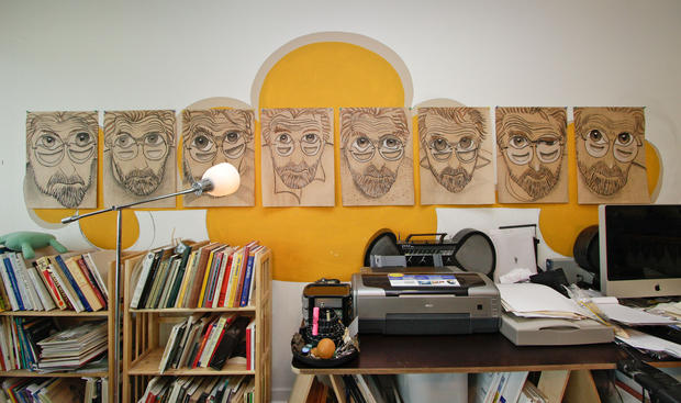 Under Gray's illustrated gaze, a functional work space uses bookshelves from IKEA.