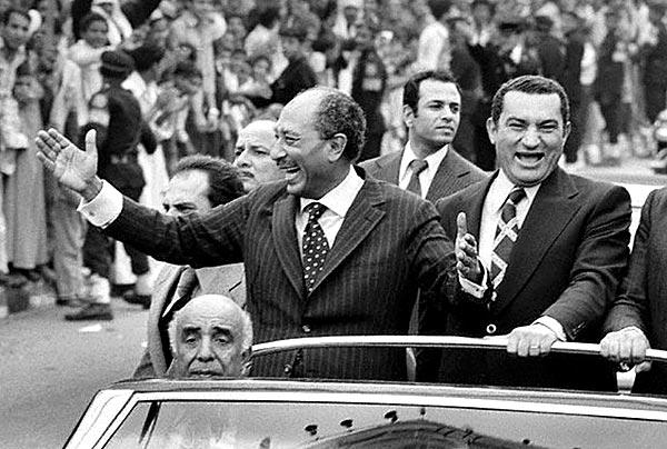 An undated picture shows then-Egyptian President Anwar Sadat, left, waving to a crowd as Vice President Hosni Mubarak, right, rides beside him.