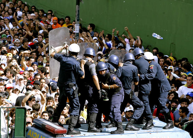 Riot police officers protect themselves as university students protest in Caracas on Nov. 1, 2007. Troops used tear gas and water cannons to disperse demonstrators who turned out by the tens of thousands to protest constitutional changes that would permit Chavez to run for reelection indefinitely.