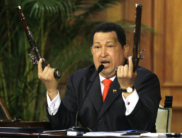 "Chavez holds two pistols that he said belonged to Venezuela's independence hero Simon Bolivar. Chavez held a ceremony on July 24, 2012, at Miraflores Palace marking the 229th anniversary of Bolivar's birth. Bolivar is the namesake of Chavez's socialist ""Bolivarian Revolution."""
