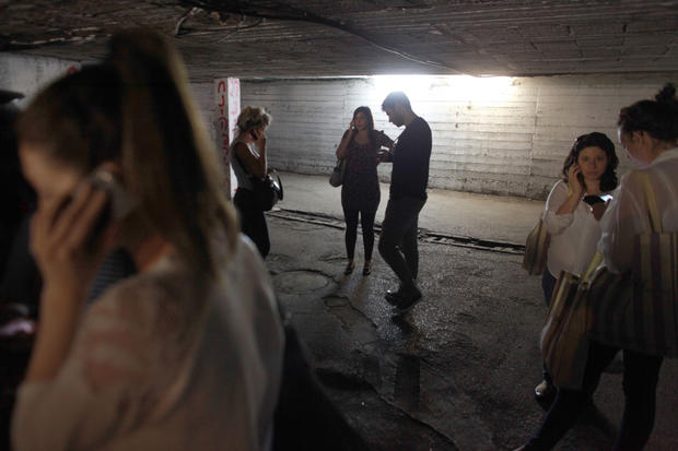 Israelis take cover in a bomb shelter in central Tel Aviv as sirens wail.