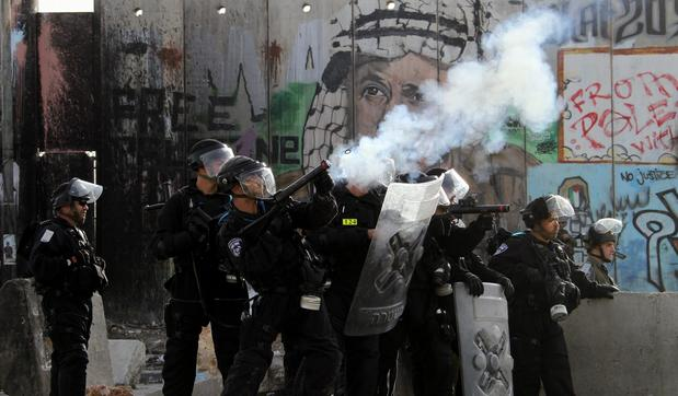 Israeli troops fire tear gas at Palestinian protesters at Qalandya checkpoint near the West Bank city of Ramallah.