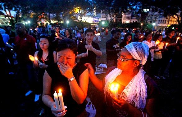 June Lee, 32, a Malaysian, left, is comforted by Rosie Salveson, 11, of Montana, right, at a candlelight vigil for Michael Jackson in Singapore.