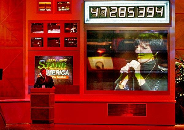 Jerry Lewis watches Liza Minnelli, her image seen on the monitor, perform during the last hour of telethon at CBS Studios in Los Angeles on Sept. 4, 1995. The event raised $47.8 million for MDA.