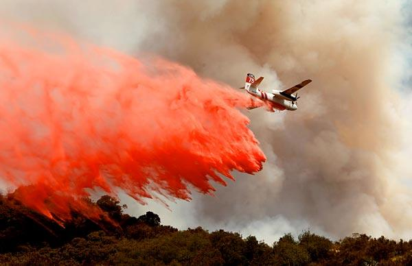 A plane drops Phos-Chek fire retardant to help slow the flames.