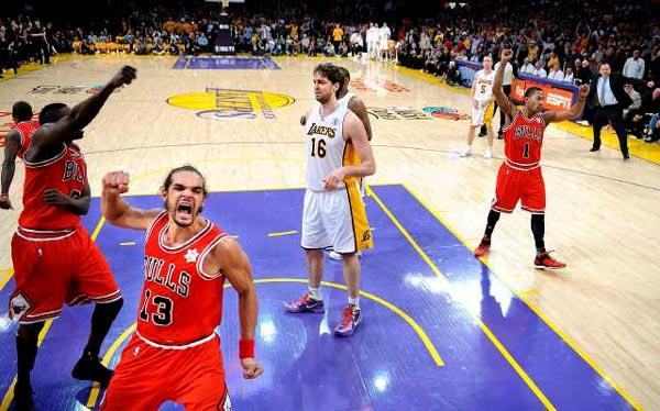 Lakers center Pau Gasol (16) is surrounded by celebrating Bulls (from left) Luol Deng, Joakim Noah (13) and Derrick Rose (1) after Kobe Bryant's last-chance shot was blocked by Deng as time expired Sunday at Staples Center.