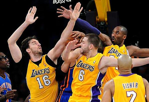 A trio of Lakers, (from left) Pau Gasol, Josh McRoberts and Kobe Bryant, try to preven Knicks center Tyson Chandler from scoring under the basket on Thursday night at Staples Center.