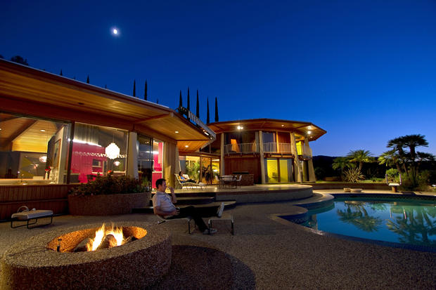 With the fire pit roaring and a Verner Panton chandelier lighting up a pink-purple kitchen with full-on 1970s style, the Loughreys' house glows at twilight. The house, designed by the Los Angeles firm Benton/Park/Candreva, consists of a single-story dodecagon with kitchen, living room, conversation pit and dining area, and a two-story dodecagon with bedrooms and a study.