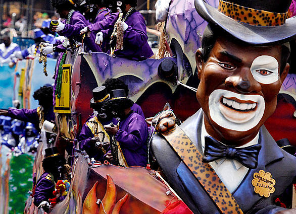 Floats from the Zulu parade roll down St. Charles Avenue in New Orleans, with participants throwing trinkets to the crowd.